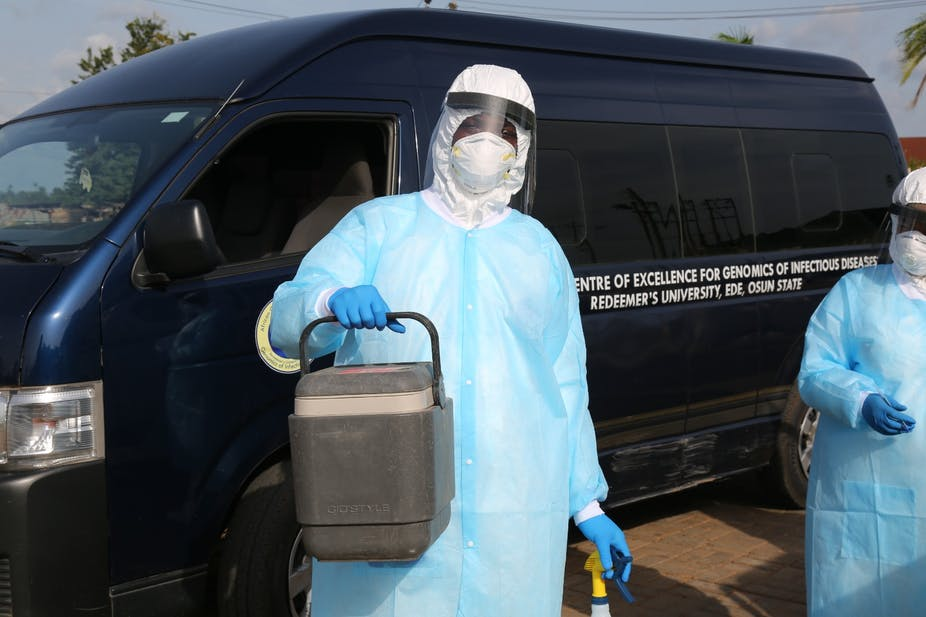 People wearing protective gear and carrying a cooler container in front of a vehicle from the African Center of Excellence for Genomics of Infectious Disease in Nigeria