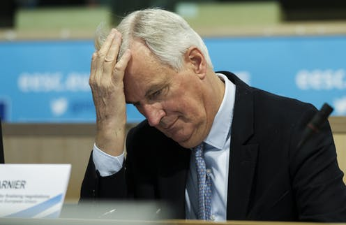 Michel Barnier holding his head with his hand.