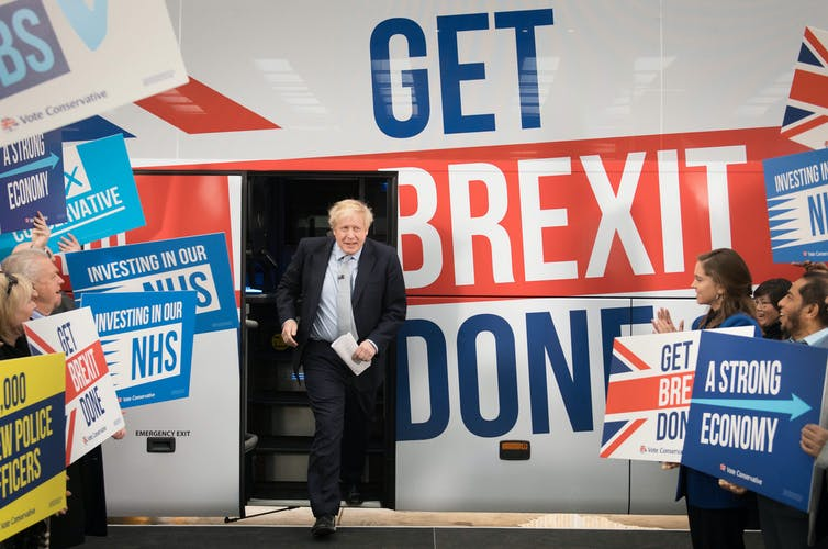 Boris Johnson steps off bus with words 'GET BREXIT DONE' surrounded by cheering crowd.