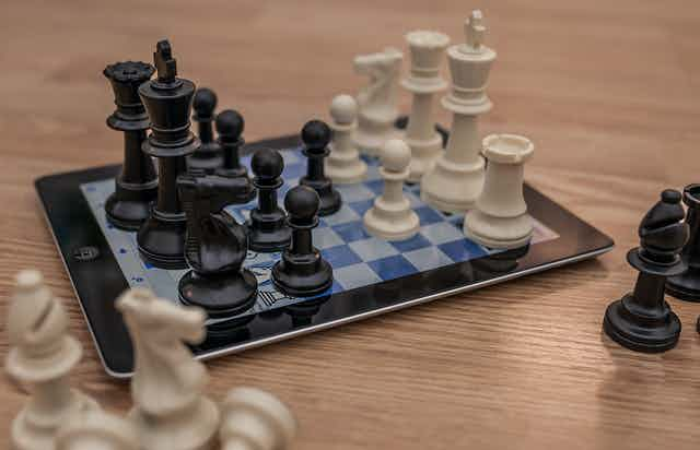 Chess pieces sitting on an iPad displaying a chess board.