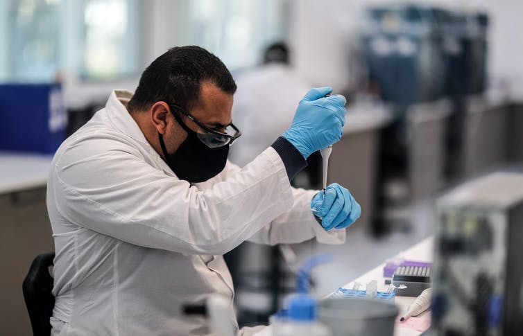 A scientist at the mAbxience's lab in Argentina using a pipette.
