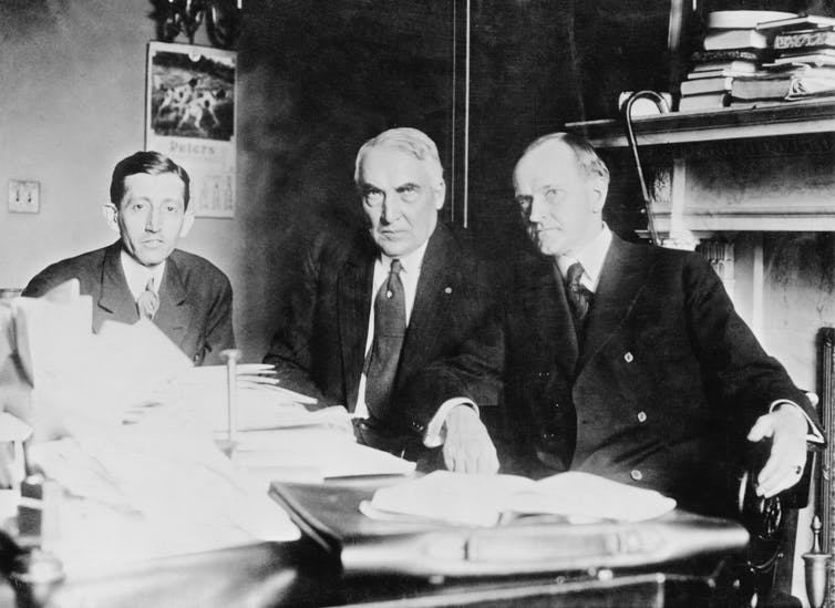 Three men at a table stacked with papers