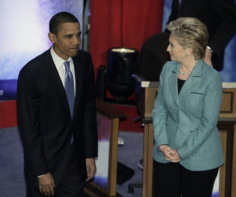 Barack Obama and Hillary Clinton stand next to each other