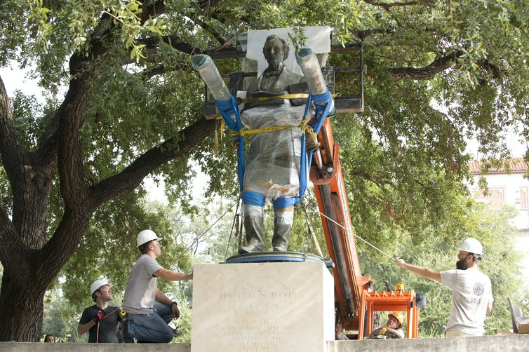 Workers in hardhats use a small orange crane to hoist a plastic-wrapped and padded bronze statue