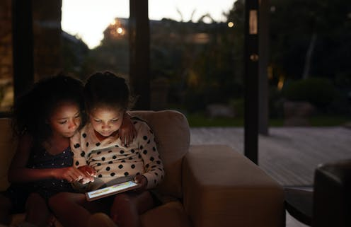 Two young girls using a digital tablet, at night