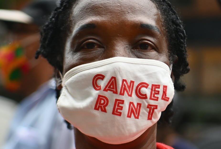 """A woman wears a face mask that says """"cancel rent."""""""
