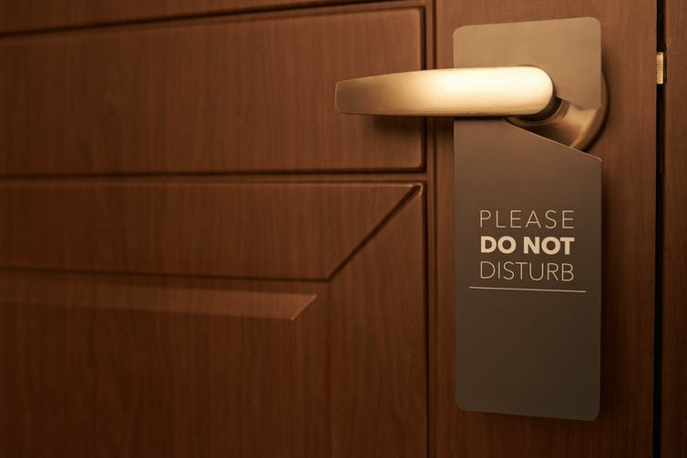 Closed door with 'Do Not Disturb' sign on door handle