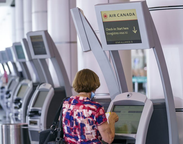 A woman uses an Air Canada self-service kiosk.