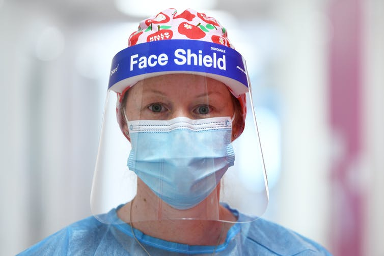 A woman in a face-shield and a mask.