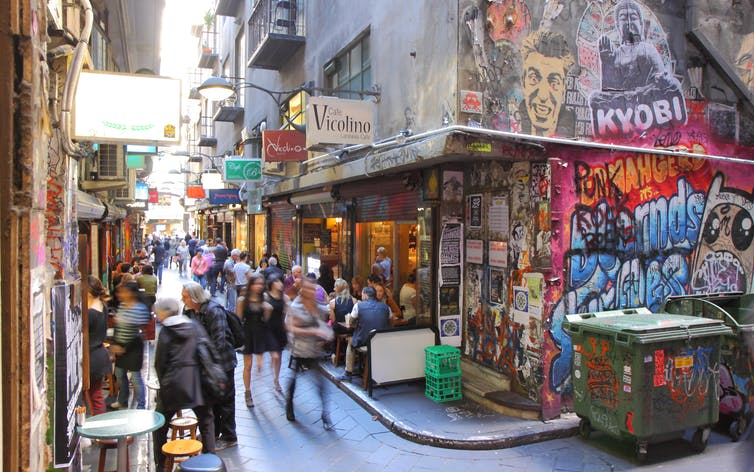 People moving through a laneway in Melbourne with cafes on each side.