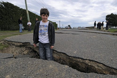 A young boy stands inside a crack in a road that was caused by an earthquake.