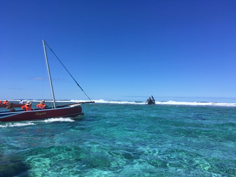 A boat in the coastal lagoon approaches the outer reef where a shipwreck looms.