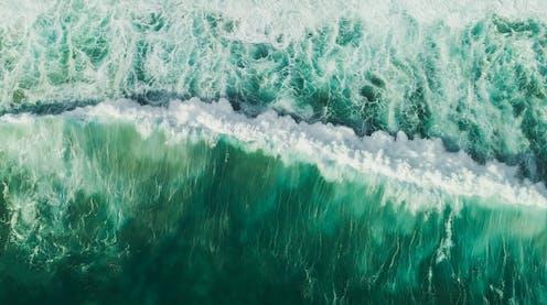 Una ola rompiente en aguas color turquesa.