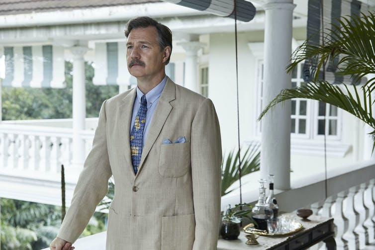 Mustachioed man in linen suit on varandah.