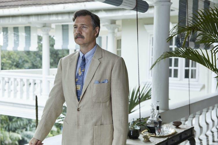 Mustachioed man in linen suit on varandah.