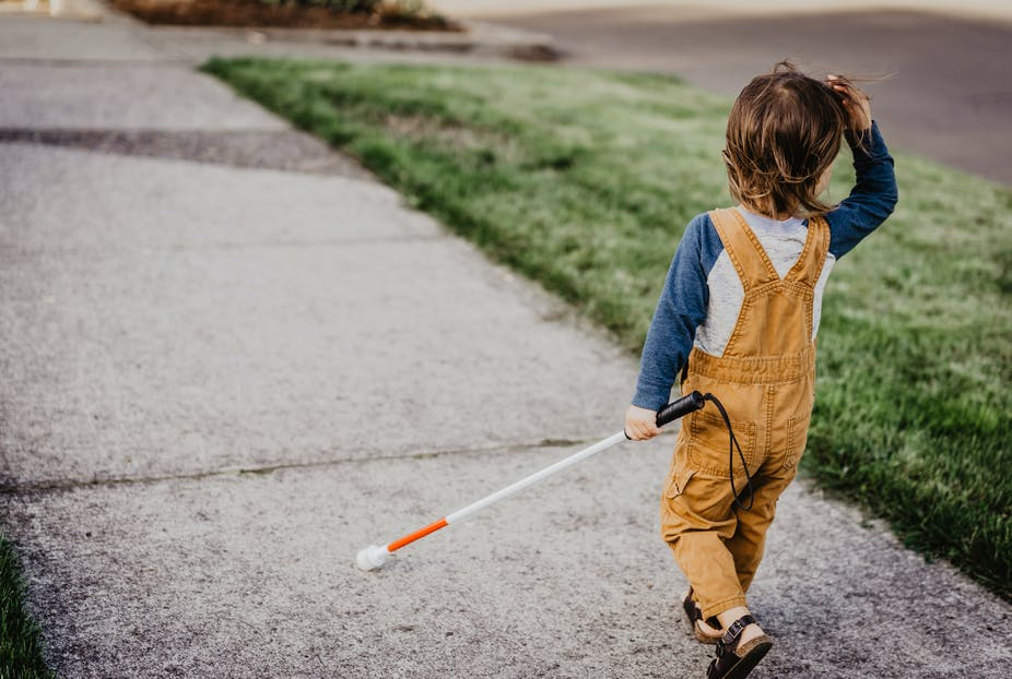 Blind child walking with cane.