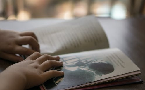 A child's hands on a book.