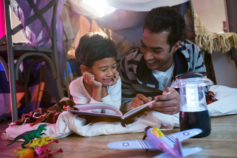 A father and son read in a blanket fort.