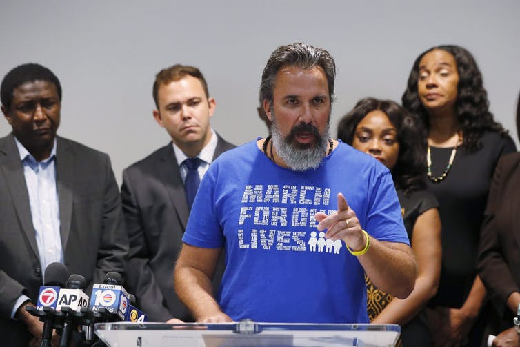 A bearded man wearing a March for Our Lives T-shirt gestures as he speaks.