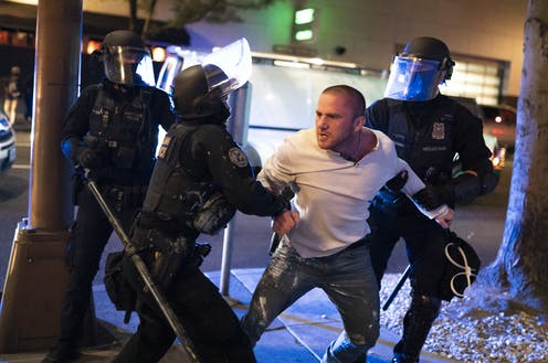 Police restrain a man in a white shirt