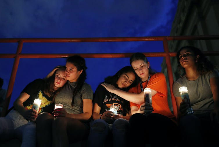 People hug each other and hold candles at a vigil