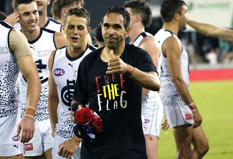 AFL player Eddie Betts wearing a t-shirt that says, 'free the flag'.