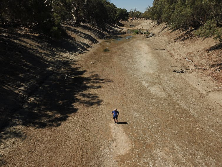 A farmer stands in the dry river bed of the Darling River