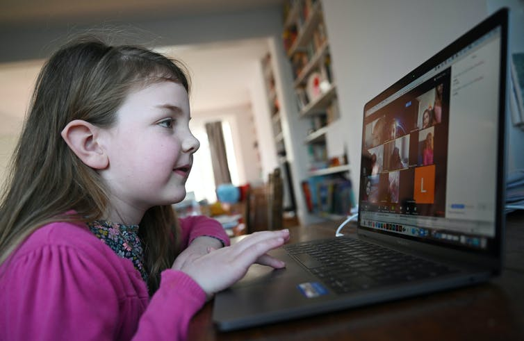 A young girl at home using a laptop.