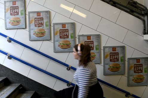 A commuter on London Underground walking past adverts selling a cheap burger