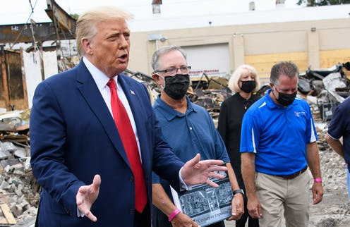 President Trump with business owners in rubble of store in Kenosha.