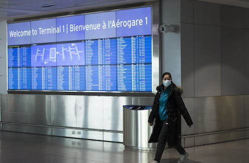 A woman wearing a mask walks past an arrivals sign at Pearson airport.