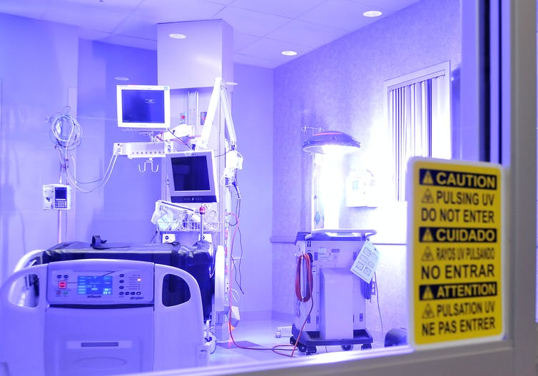a robot emitting ultraviolet light in an empty hospital room