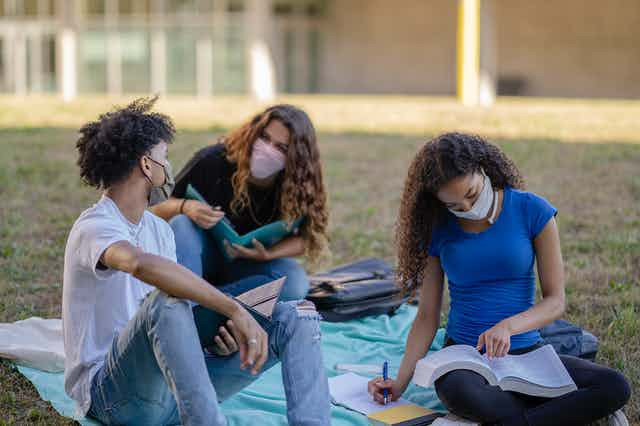 Three college students wearing masks study outside on a grass plain.