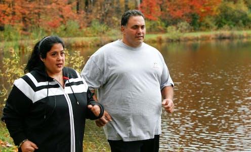 A ma and woman walk by a lake.