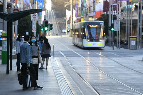 Two people wearing masks in Melbourne with passing tram