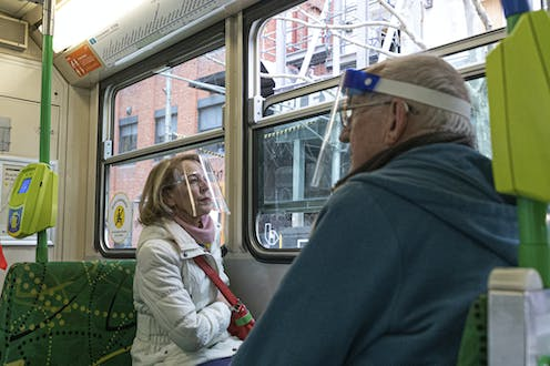 Two commuters on a Melbourne tram wearing face shields.