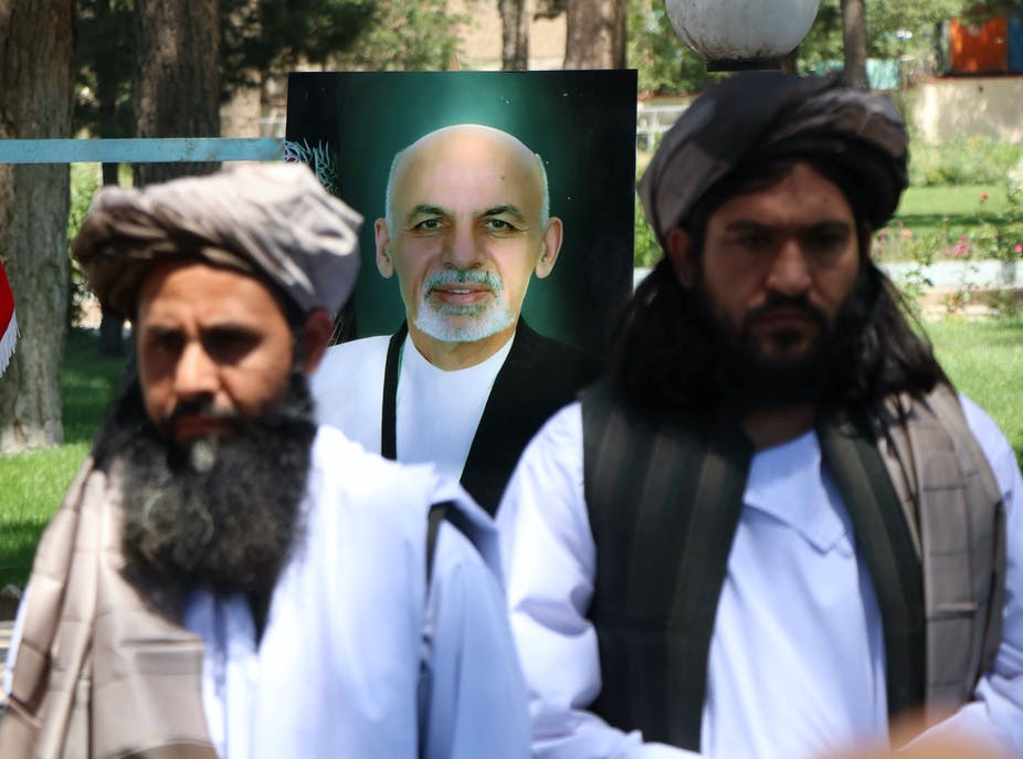 Two Taliban stand in front of a poster of Afghan president Ashraf Ghani