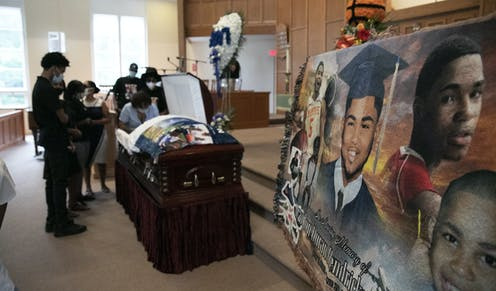 Mourners stand over the casket of 17-year-old Brandon Hendricks-Ellison while a photo montage of the 17-year-old is in the foreground.