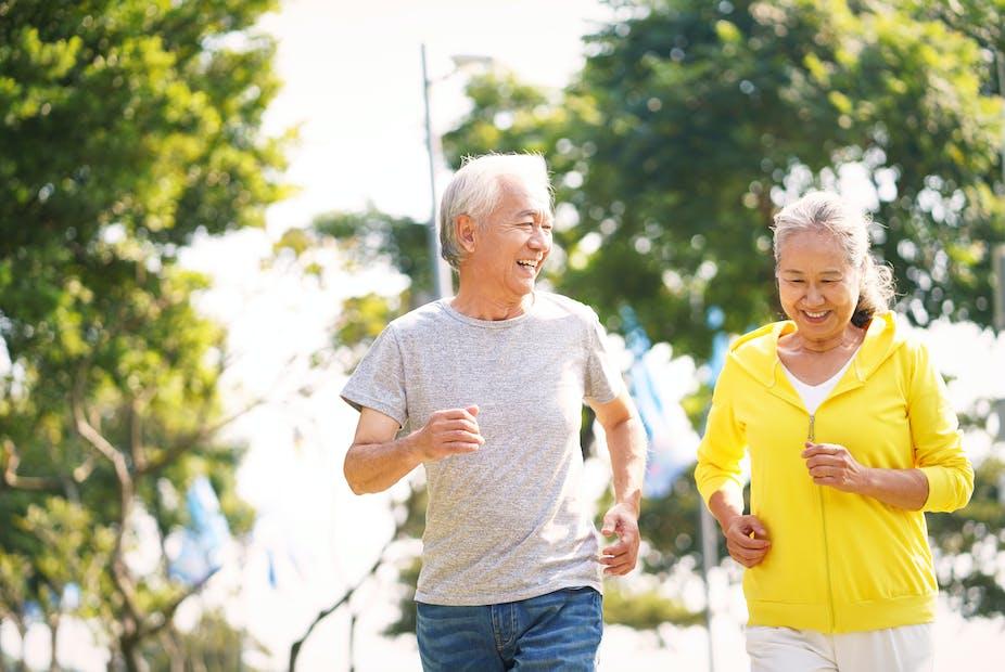 Elderly man and woman jog together.