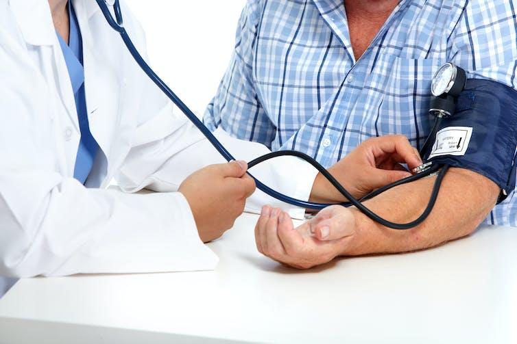 Doctor midiendo la presión arterial de un hombre.