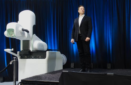 Picture of Elon Musk at Neuralink presentation with robot.