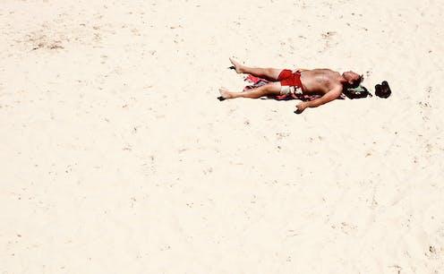 Man sunbathes on beach