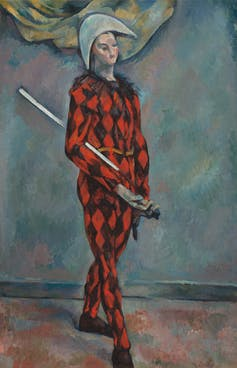 Harlequin in a red and black diamond pattern jumpsuit holding a sword.