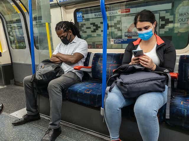Man and woman on London Underground wearing masks.
