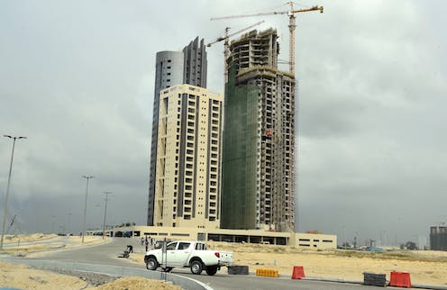 A car drives in front of modern skyscrapers under construction with large cranes alongside