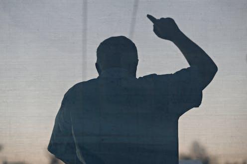 Contraluz de un hombre durante un discurso con gesto amenazador.