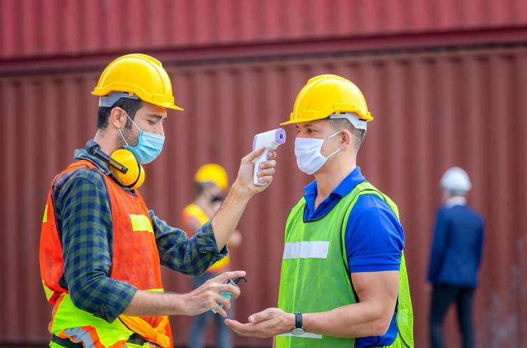 Factory worker takes temperature of colleague and holds out hand sanitiser.