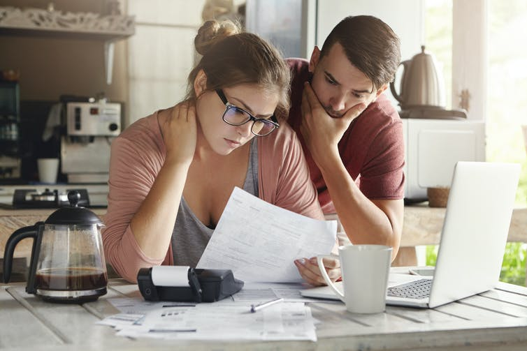 Young couple in kitchen looking at household bills