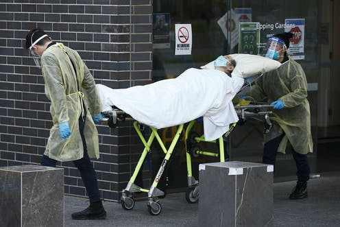 Two health workers transporting an unwell aged care resident