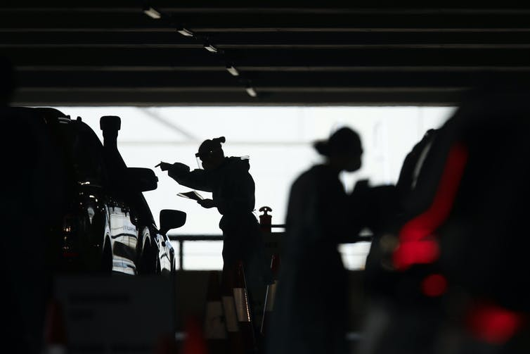 Two figures in PPE in silhouette lean towards cars.